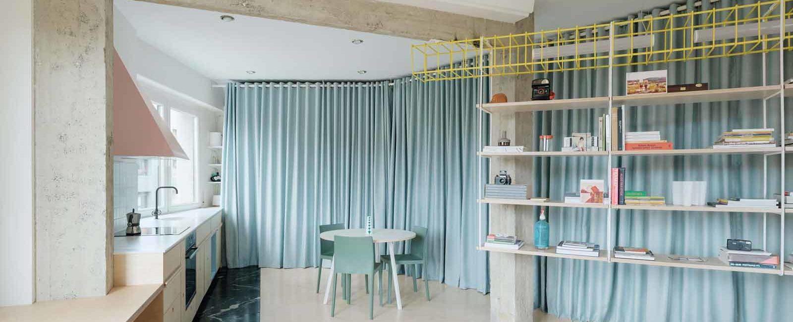 Lo studio Azab sostituisce le pareti divisorie con tende azzurre in un appartamento di Bilbao
