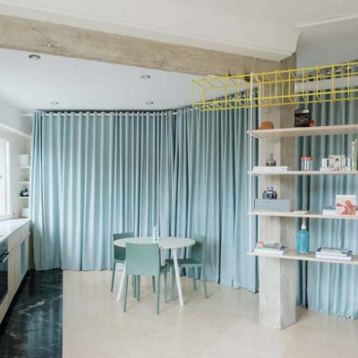 Azab replaces partitions with theatrical pale-blue curtains in a Bilbao apartment